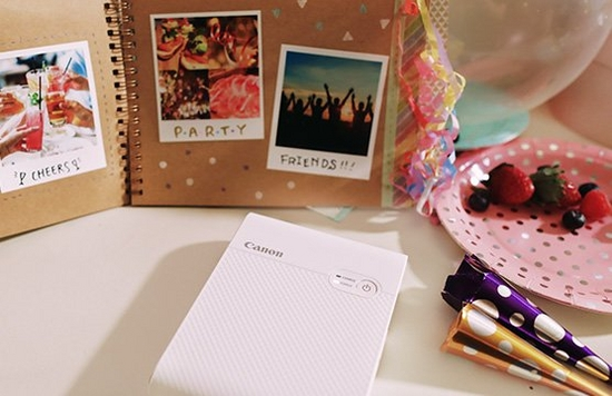 A scrapbook with printed photos propped against a wall. In front, a Canon Selphy Square QX10 printer.