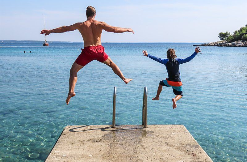 dad and son jumping into the ocean