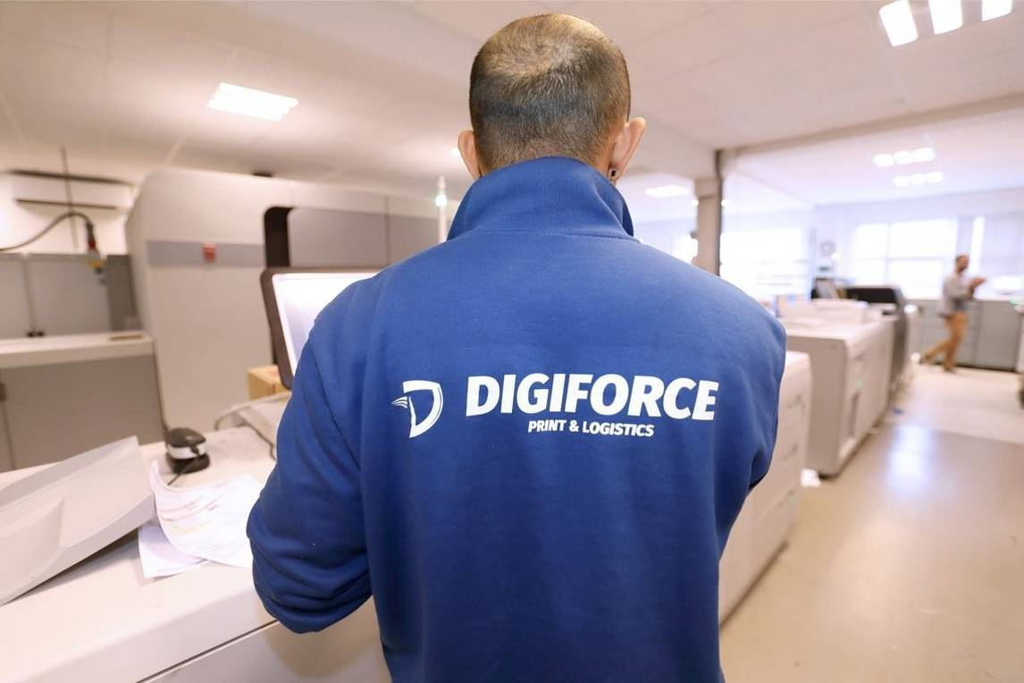 Back of a man wearing a jumper with the Digiforce name and logo using an inkjet printing press