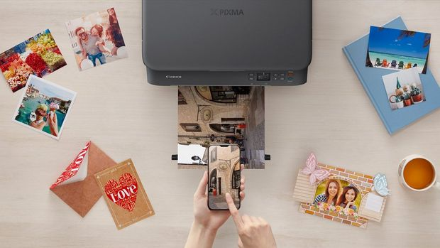 A flat lay image of a PIXMA printer, printing out holiday pictures, surrounded by other printed pictures.