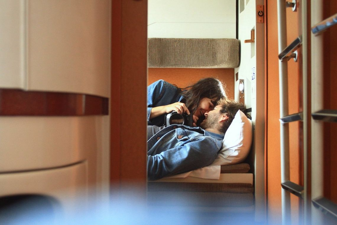 The photographer lays on a sleeper train bed embracing with her husband, holding a camera in her left hand, taking a self-portrait in a mirror