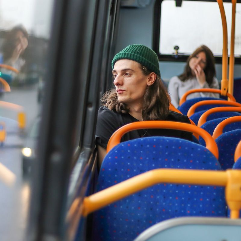 Boy stares out of bus window, showing depth of field