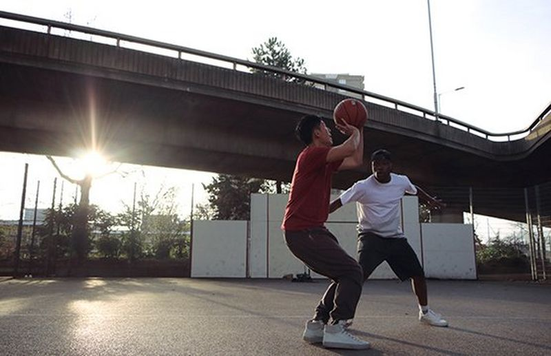 2 men playing basketball with sunlight behind them