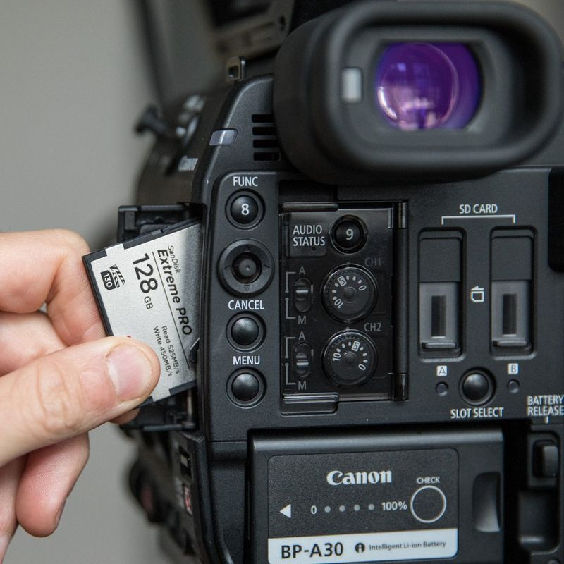 128 GB SD card being slotted into Canon video Camera.