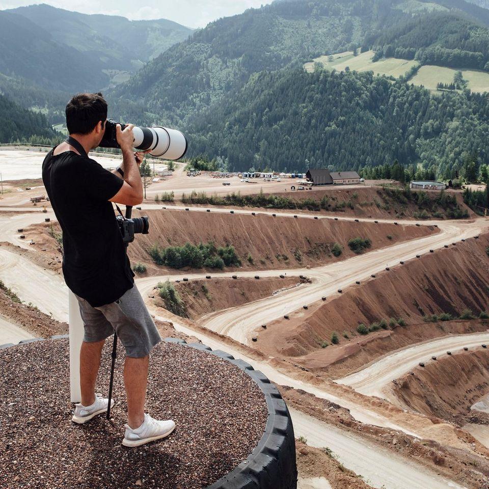 Мужчина стоит на платформе над песчаной трассой, у него в руках камера Canon EOSR3 с прикрепленным супертелеобъективом.