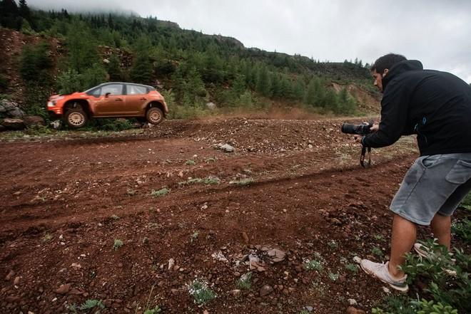 Мужчина в шортах и темной куртке фотографирует раллийный электромобиль, который быстро едет по каменистой местности.