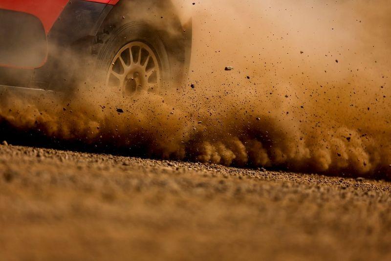Крупный план заднего колеса раллийного болида, вздымающего в воздух клубы пыли и грязи.