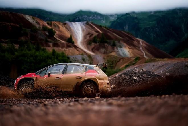Раллийный электромобиль быстро едет по каменистой местности, вздымая клубы грязи и пыли.