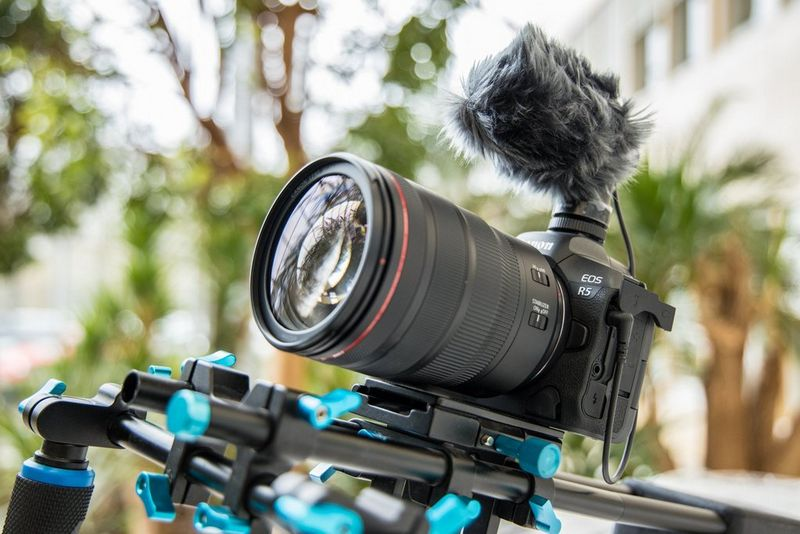 A Canon EOS R5 attached to a camera rig and with a microphone on top.