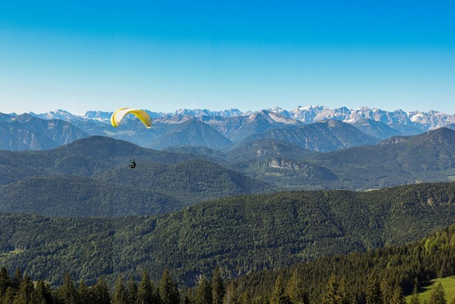 A paraglider with a yellow canopy high above the lush German Alps.