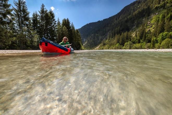 Мужчина сплавляется в каноэ по реке в окружении деревьев.