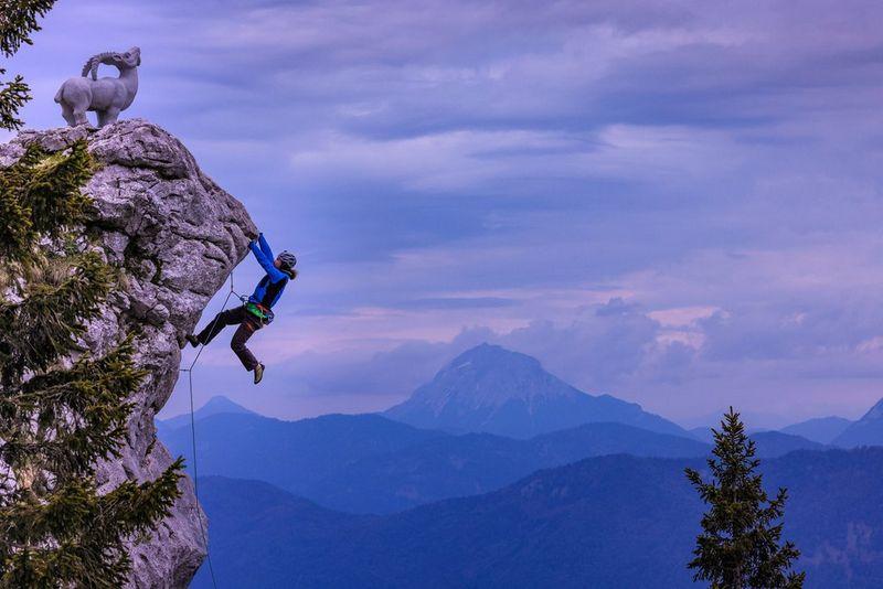 Альпинист держится за выступ, изучая поверхность скалы в Баварских Альпах при свете вечернего солнца.