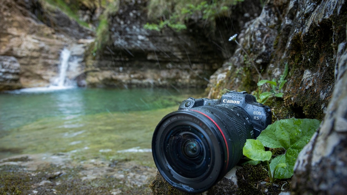 A Canon EOS R5 with Canon RF 15-35mm F2.8L IS USM lens on the bank of a pool with a waterfall in the background.