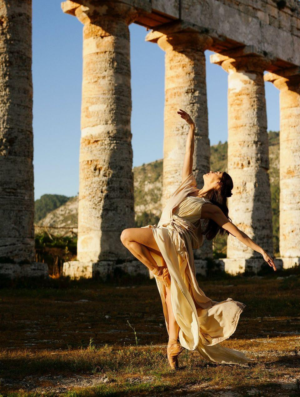 Balerin pozând într-o zonă deschisă, înconjurată de coloane