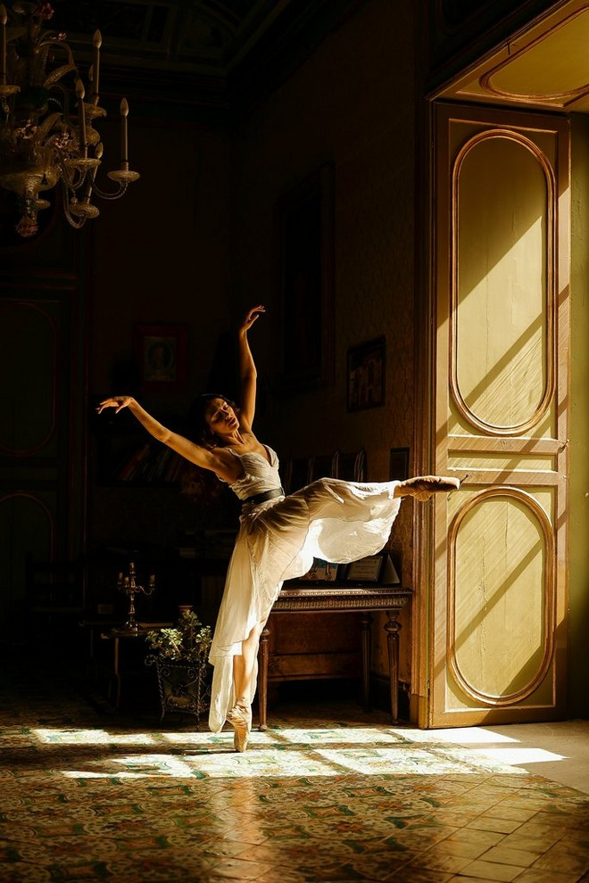 girl striking a graceful ballet pose in a dimly lit room