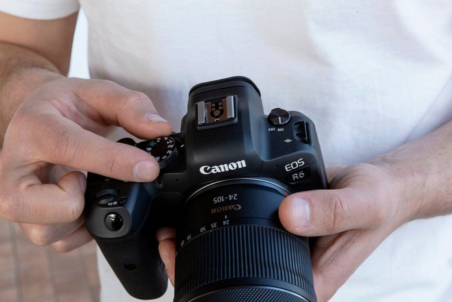 A man holds a Canon EOS R6 and adjusts the mode dial on top.