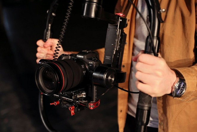 A Canon EOS R6 being used for filming in a gimbal held by a man's hands on each side.