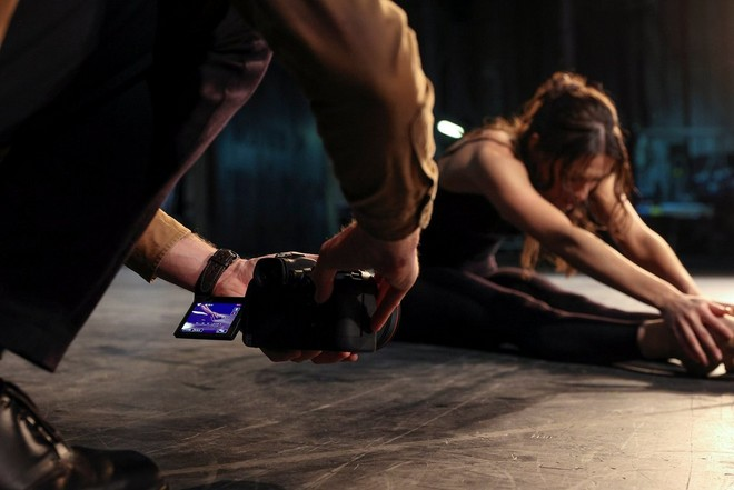 A photographer holds an EOS R6 close to floor level, taking advantage of the Vari-angle screen to photograph a dancer stretching.