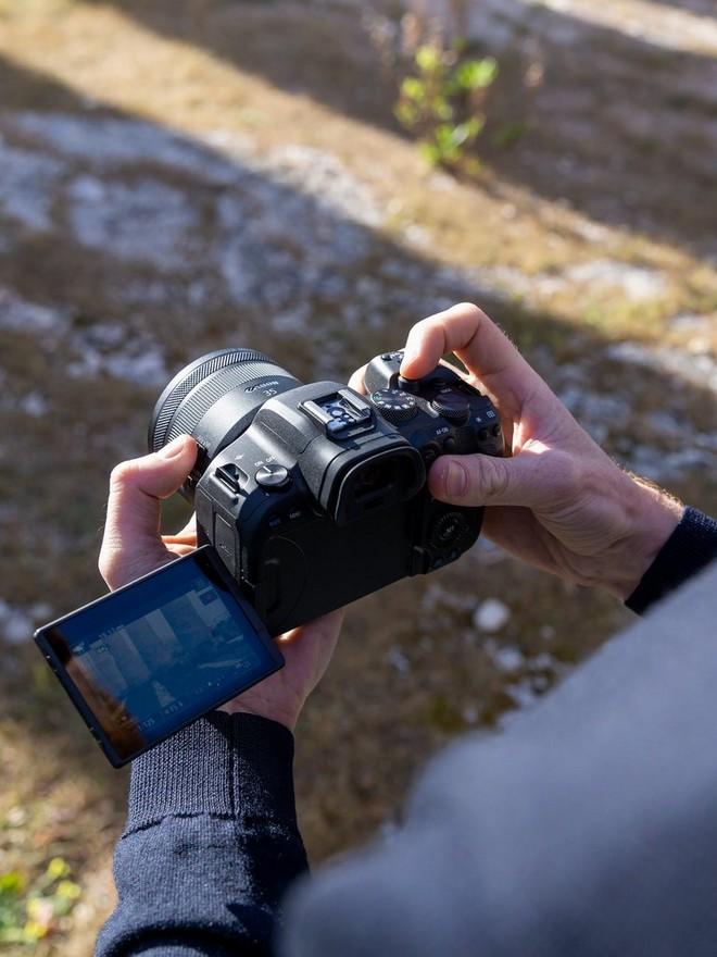 Mâini care ţin un Canon EOS R6 într-un cadru natural