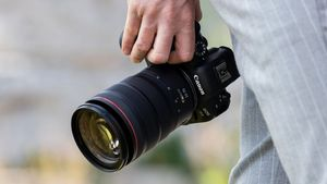 A man holding a Canon EOS R6 camera by his side.