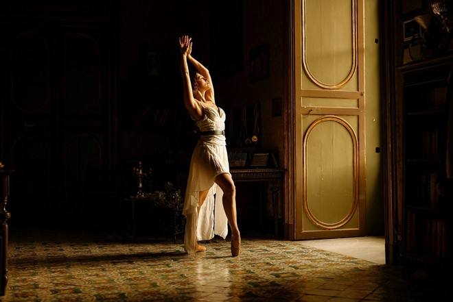 A ballerina poses in the light from an open door. The rest of the room is in shadow.