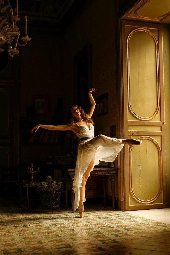 A ballerina dances in the light from an open door. The rest of the room is in shadow.