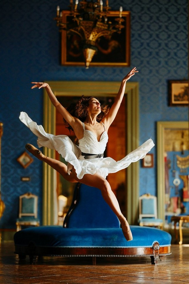 A ballerina leaps across an ornately decorated room.