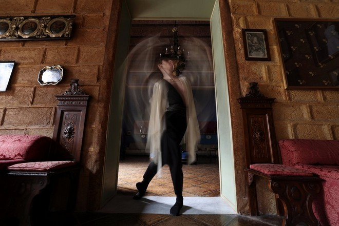 A dancer stands in a doorway of an ornately decorated room, arms blurred by motion.
