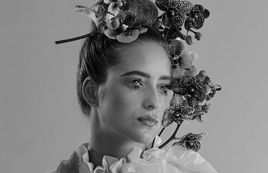 A black and white portrait of a lady wearing a flower crown.