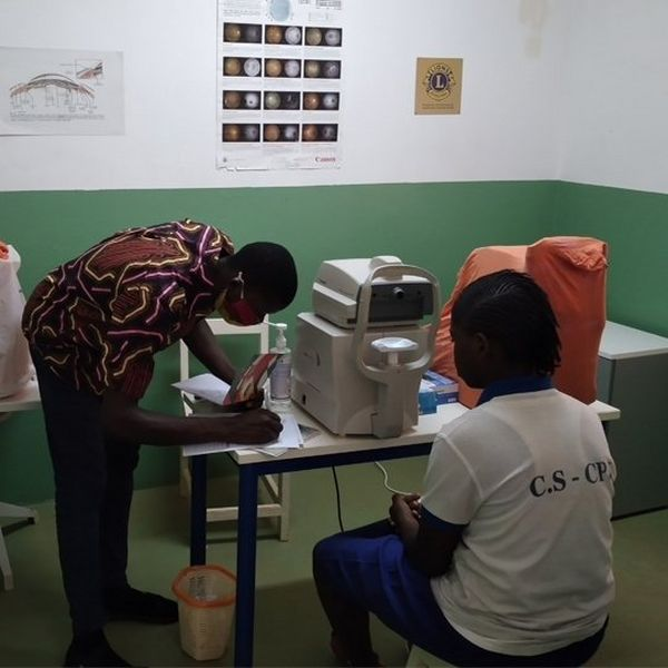 Two people in a green and white walled medical examination room. One sits in front of a machine, ready for an eye examination, the other is bent over and making notes.