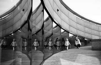 A mother and child play outside in front of series of mirrors.