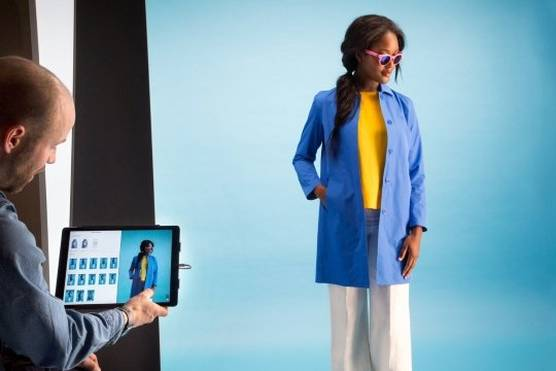 A model in sunglasses and a blue coat being photographed in a StyleShoots photography machine.