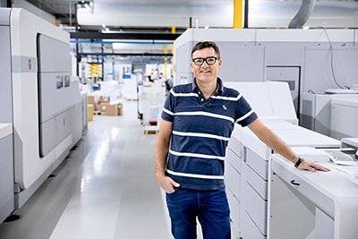 Male standing next to large printing machine