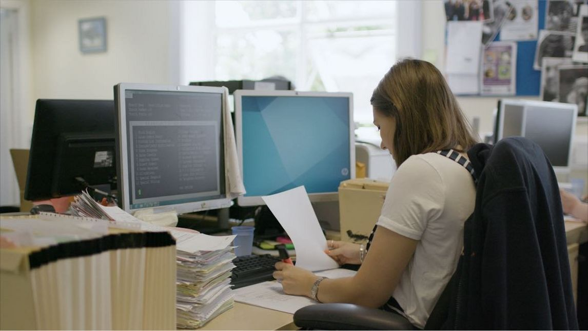 Woman in office processes Accounts Payable paper invoices in front of computer