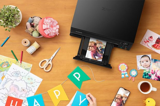 A Canon PIXMA TS6340 printer surrounded by papercraft materials, pencils and a pair of scissors.