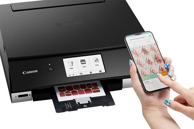 A woman holds a smartphone above a Canon PIXMA TS8340 printer.