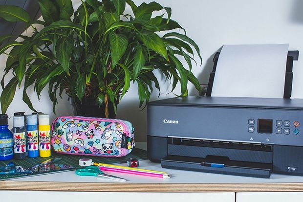 A Canon PIXMA TS5340 printer on a desk next to a pencil case and stationery.