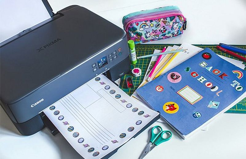 A Canon PIXMA TS5350 Series printer next to school books, a pencil case and a pair of scissors.