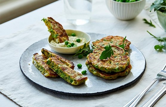 A plate of pea fritters garnished with peas and rocket leaves.