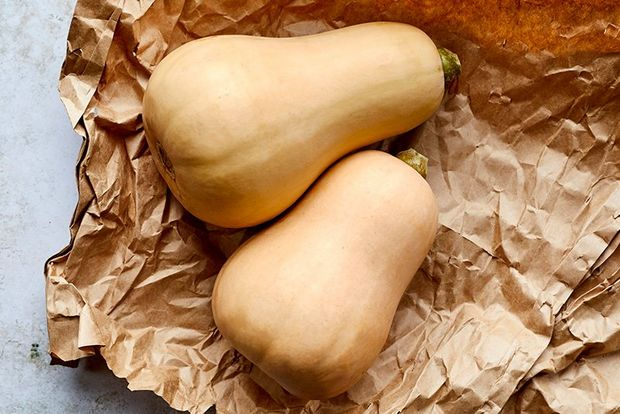 Two butternut squash on a crumpled sheet of brown paper.