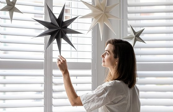 A woman standing in front of shuttered windows touches a paper star hanging from the ceiling.