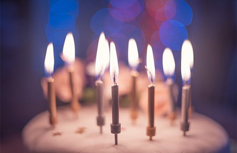 A close-up of some candles on a cake, with blurred lights in the background.