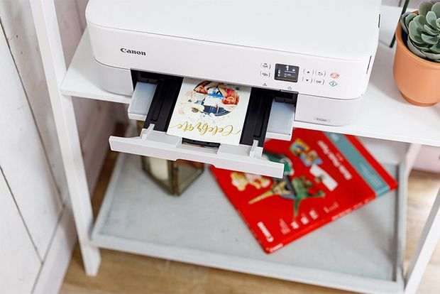 A personalised card on the paper tray of a Canon printer.