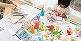 A child sat at a table with an adult creating colourful papercrafts using a Canon printer.