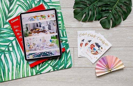 A tablet displaying the Creative Park app sits on botanical themed paper, next to custom invitations and colourful bunting.