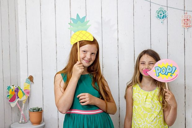 Two girls hold photo booth party props printed from Creative Park