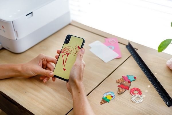 A woman applying a cut-out printed sticker to the back of her smartphone.