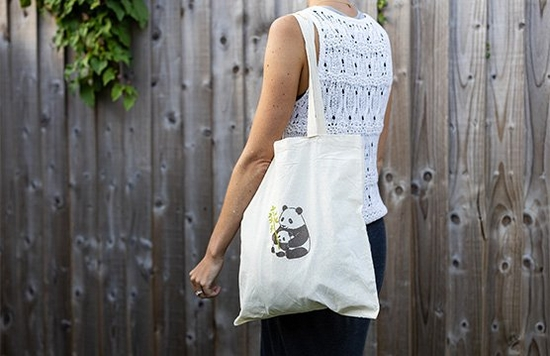 A woman wears a cotton tote bag, adorned with an iron-on transfer of a panda.
