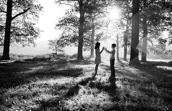 Two children silhouetted against a woodland background by the low sun streaming through the trees.
