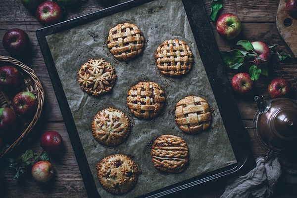 Eight small pastry topped pies on a tray surrounded by apples.